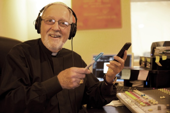 Father Eugene broadcasting at Cosmos-FM studios. His radio program, Matters of Conscience, has aired for 18 years.